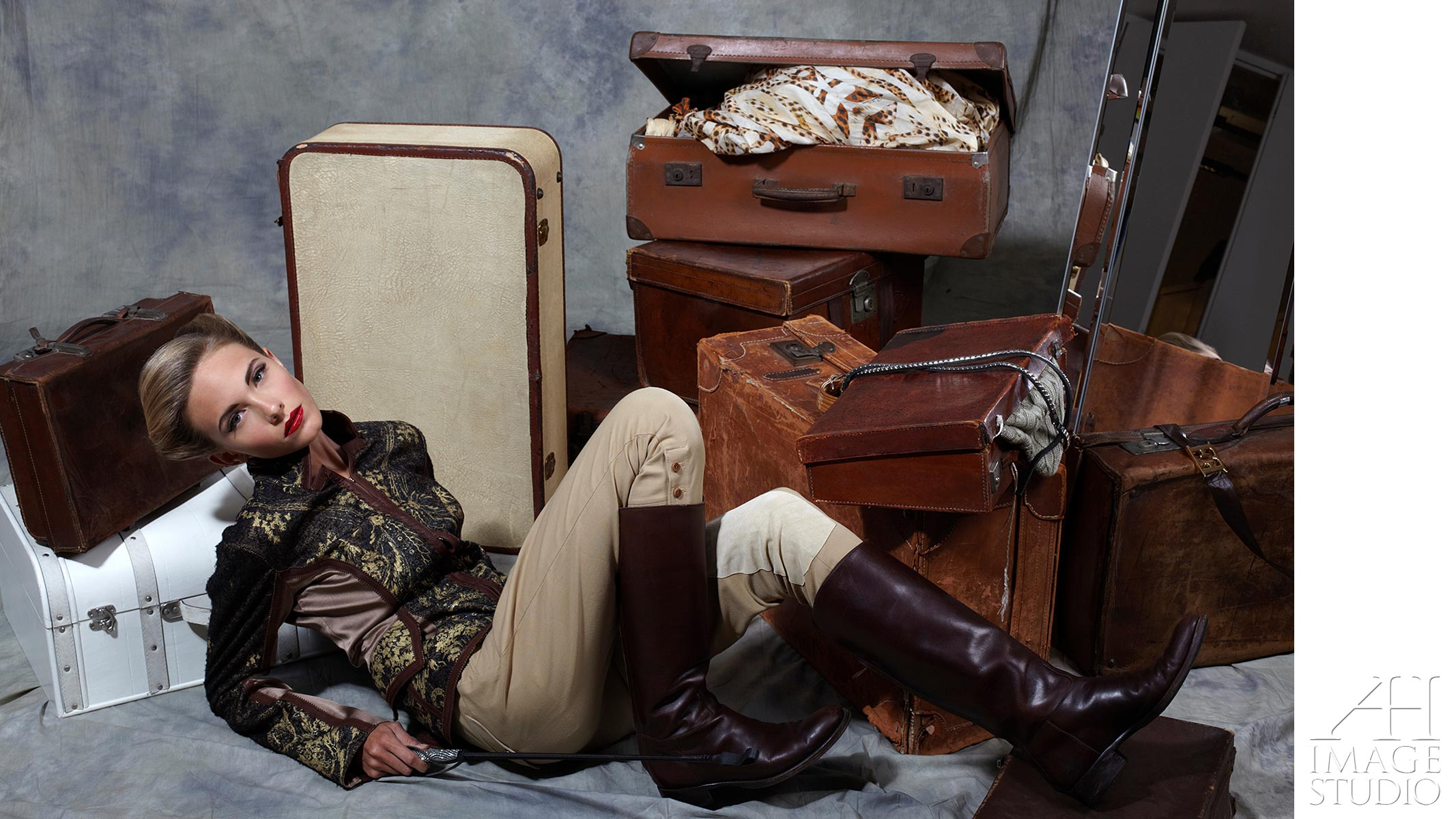fashion photo shot with suitcases horse riding boots